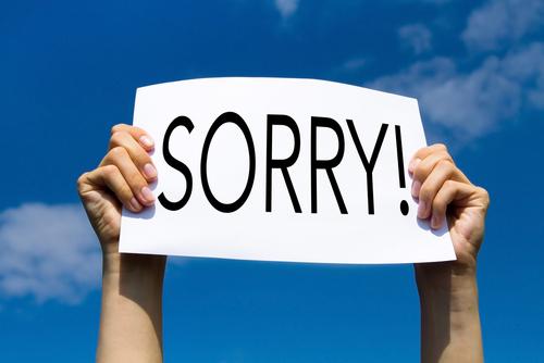 Hình ảnh hai tay cầm chữ xin lỗi